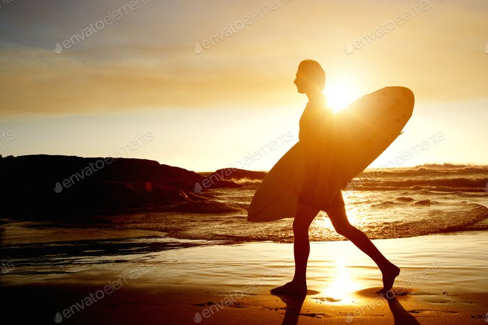Surfer walking on beach with surfboard during sunset