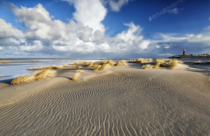 beautiful blue sky over North sea beach with lighthouse