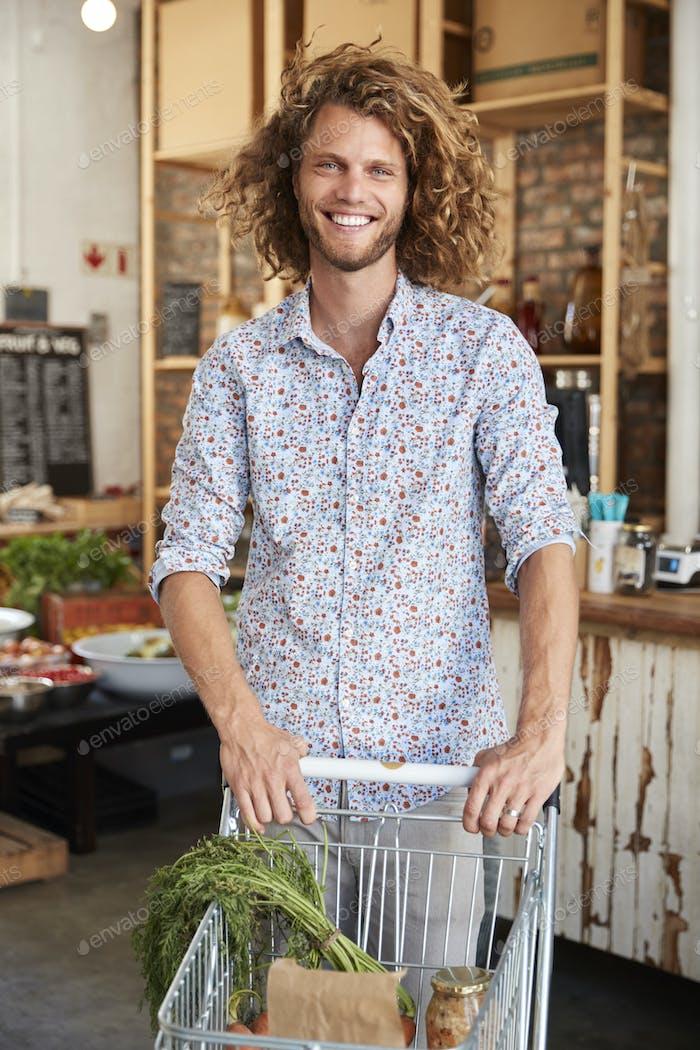 Porträt von Mann mit Trolley Kauf von frischem Obst und Gemüse in Kunststoff Free Lebensmittelgeschäft