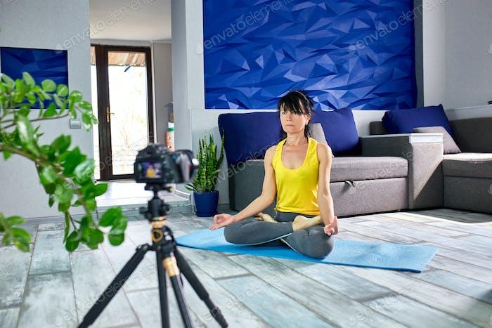 Blogger Senior Frau mit schlanker Körperform in Sportbekleidung tun Yoga zu Hause.
