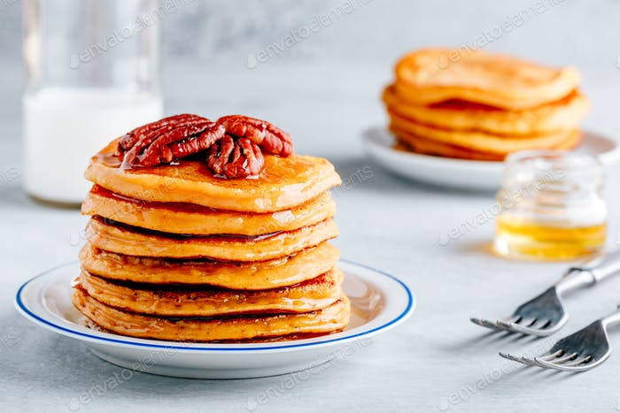 Pumpkin pancakes with pecans and maple syrup or honey