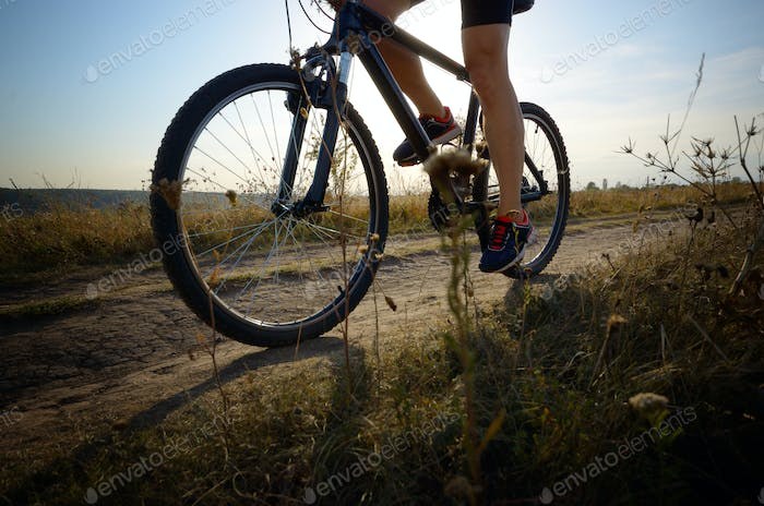 Male cyclist driving by rural dirt road outdoors. Low angle view