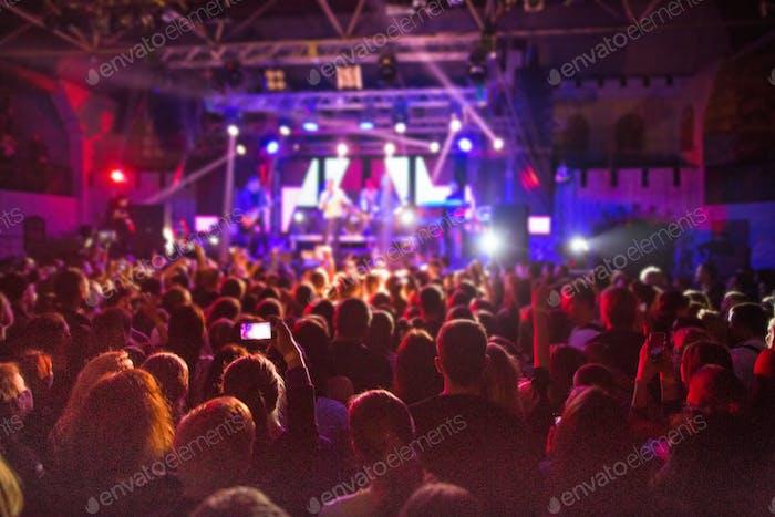 Die Silhouetten der Konzertmenge vor hellen Bühnenlichtern