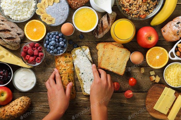 Female hands spreading butter on bread. Woman cooking breakfast. Healthy breakfast ingredients, food