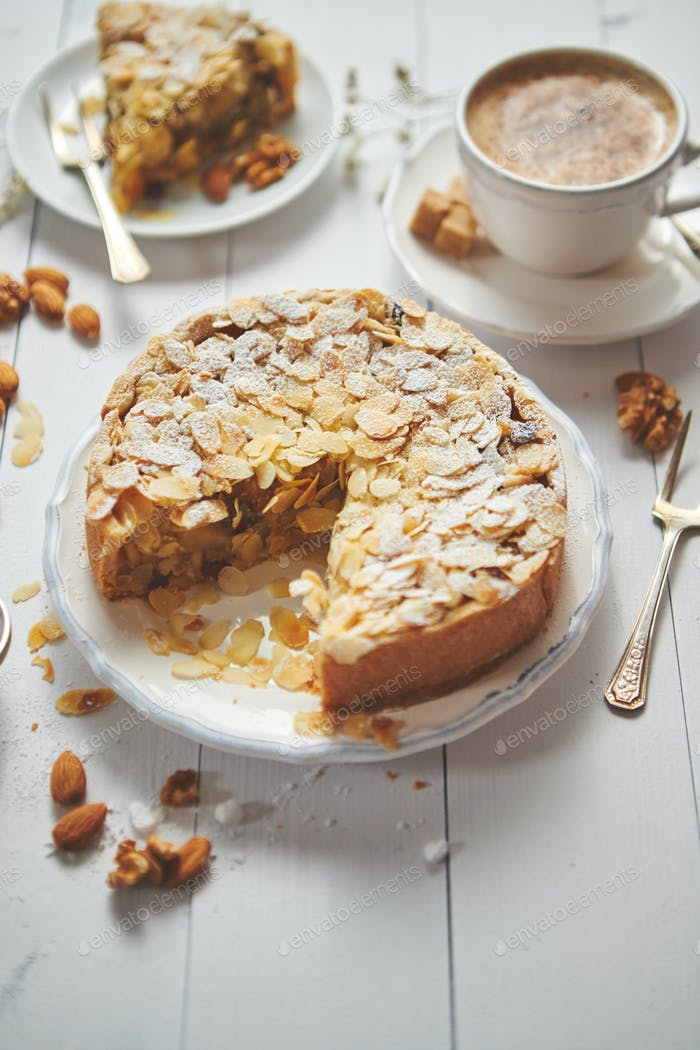 Whole delicious apple cake with almonds served on wooden table