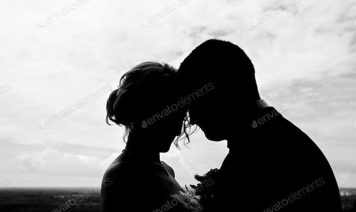 Silhouettes of couple against the  sky.