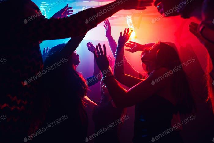 Eine Menschenmenge in Silhouette hebt ihre Hände gegen buntes Neonlicht auf Partyhintergrund