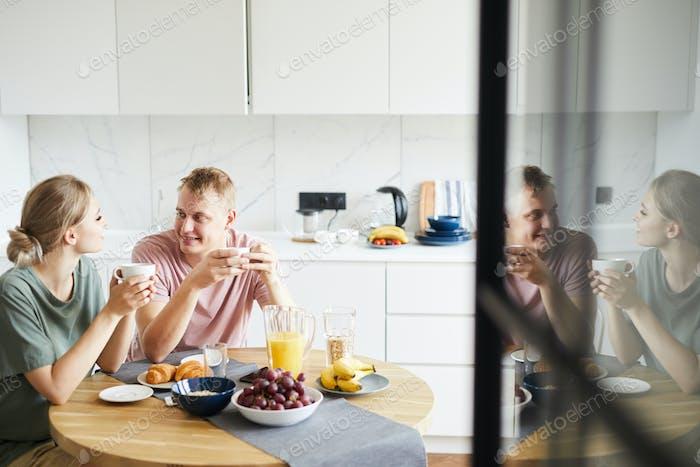 Junge erholsame Ehegatten mit Brunch und Tee in der Küche