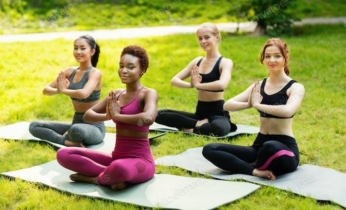 Yoga for mind control. Peaceful girls enjoying their yoga meditation on green lawn at park