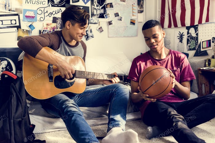 Teenage boys hanging out in a bedroom music and sports hobby concept