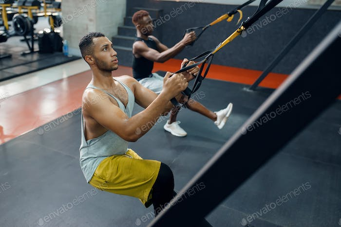 Two athletes at exercise machine, training in gym