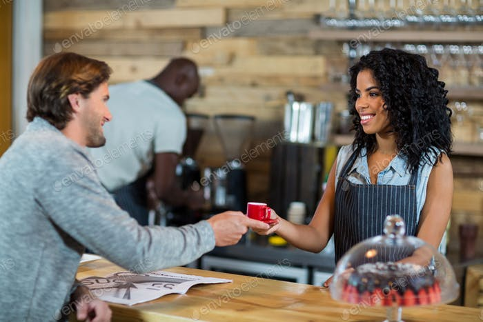 Waitress serving a cup of coffee at counter
