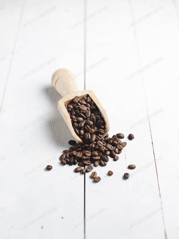 coffee beans in wooden scoop with white wood background