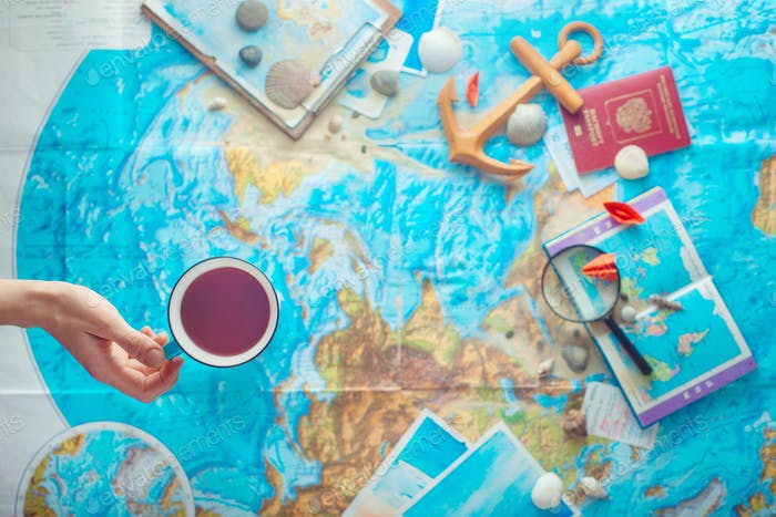 Adventure and traveling flat lay with a map, wooden anchor, paper airplanes, passport and a