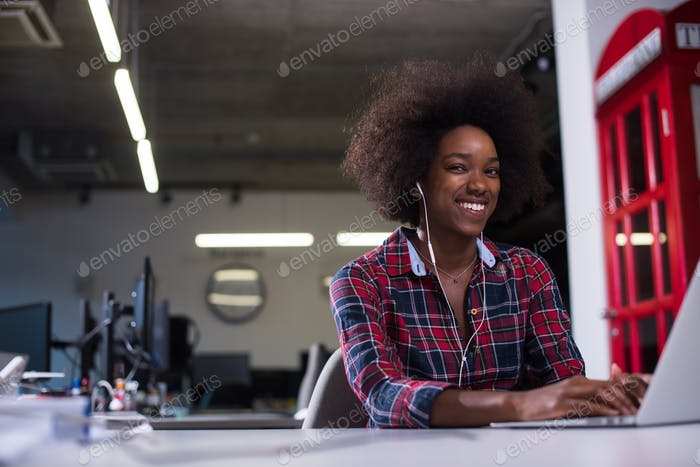 black woman in modern office speeking on phone over earphones