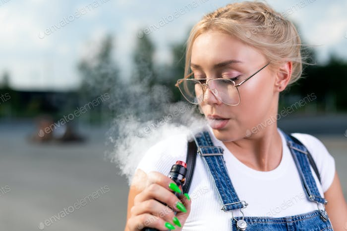 Portrait of young woman vape an electronic cigarette outdoor