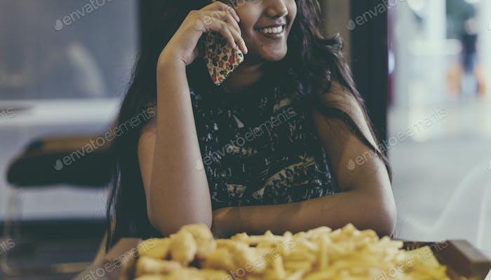 Close up of adolescente girl hablando en un teléfono comiendo papas fritas Concepto de cultura juvenil