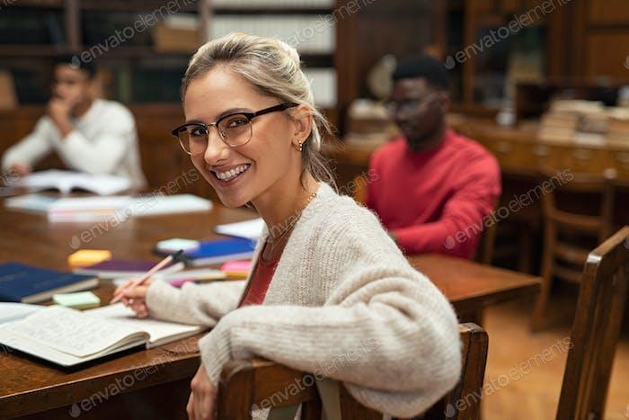 Glückliche weibliche Studentin in der Bibliothek