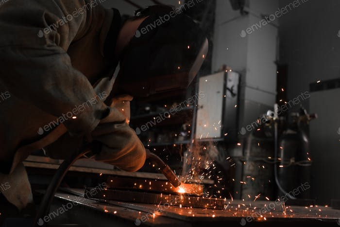 Manufacture Worker Welding Metal With Sparks at Factory