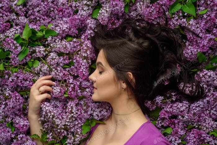 Portrait of a young woman surrounded by lilacs. A woman is standing sideways.