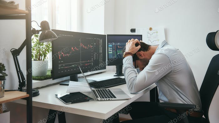 Feeling sad. Depressed young businessman or trader in formalwear keeping head in hands while working