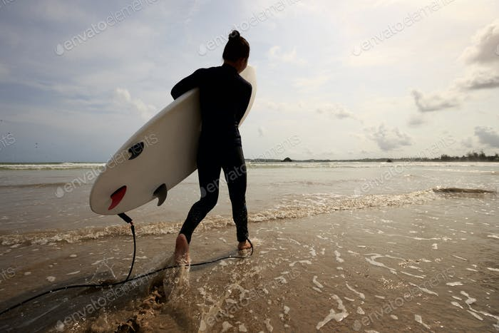 Surfer with surfboard running on beach
