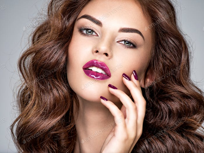 Beautiful and stunning woman with  purple lipstick on lips and f