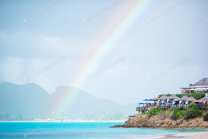 Tropical beach with turquoise water in the ocean, white sand and colorful rainbow
