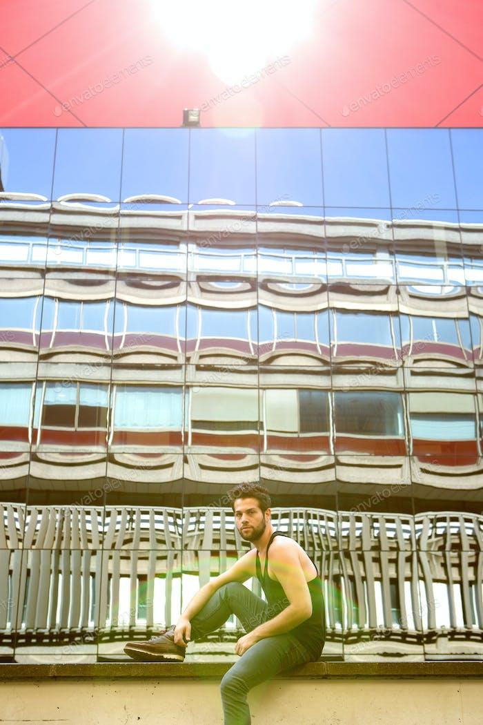 Coole Kerl sitzen im Freien in städtischen Bereich