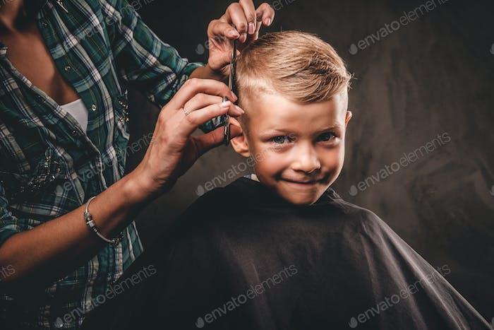 Cute preschool boy getting haircut.
