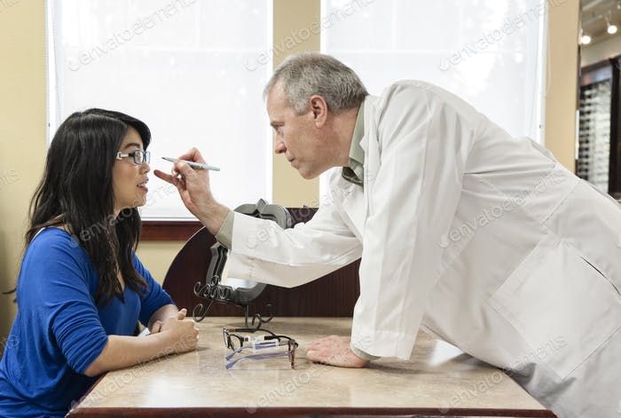 Caucasian male ophthalmologist working with an asian woman who is purchasing a new pair of glasses.