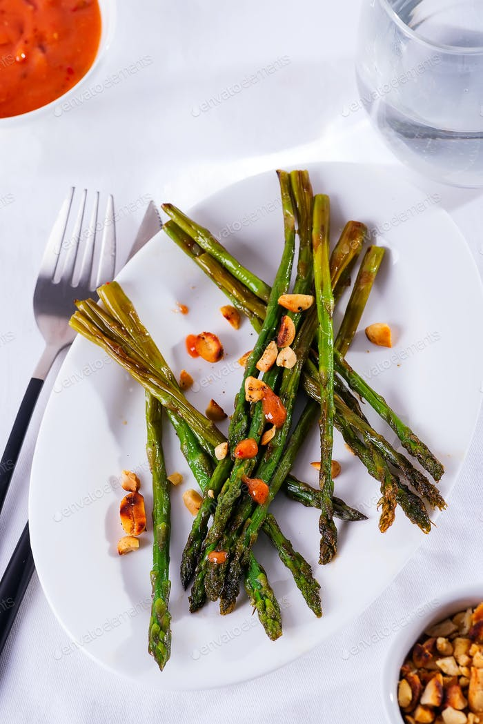 Asparagus roasted in olive oil with crushed walnuts and sauce on a white plate. Vegetarian food