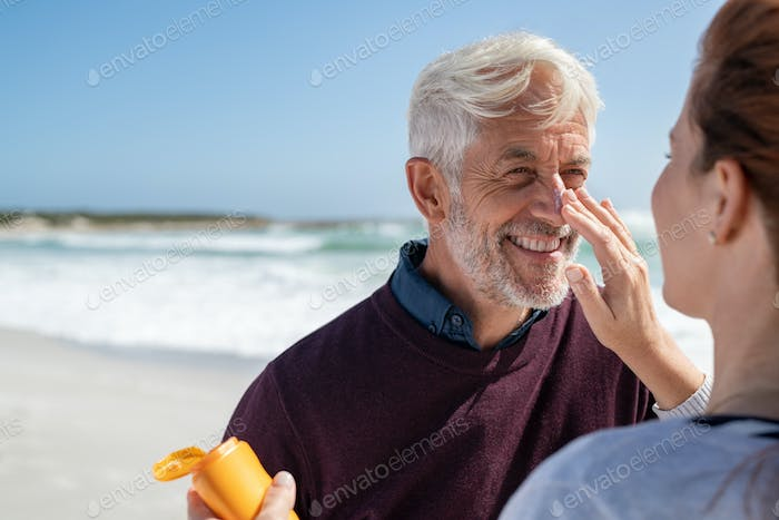 Woman applying sunscreen on senior man nose