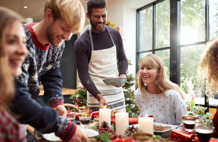 Group Of Friends Sitting Around Dining Table At Home As Christmas Dinner Is Served