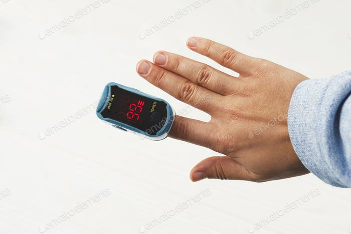 Pulse Oximeter on adult hand on white background, measuring blood oxygen level, tests saturation