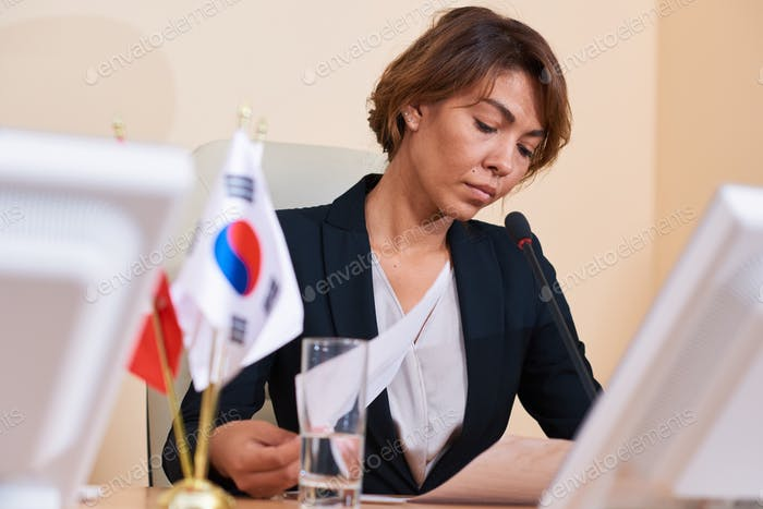 Young serious well-dressed businesswoman concentrating