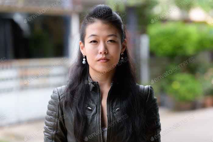 Gesicht der schönen asiatischen rebellischen Frau im freien