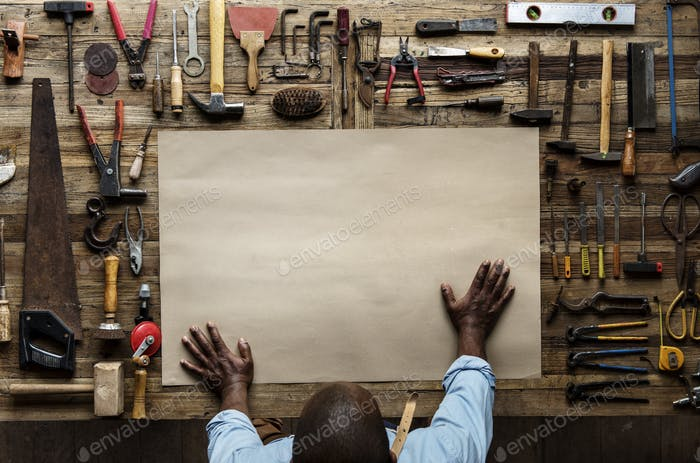 Aerial view of carpenter craftsman with blank paper on tools set
