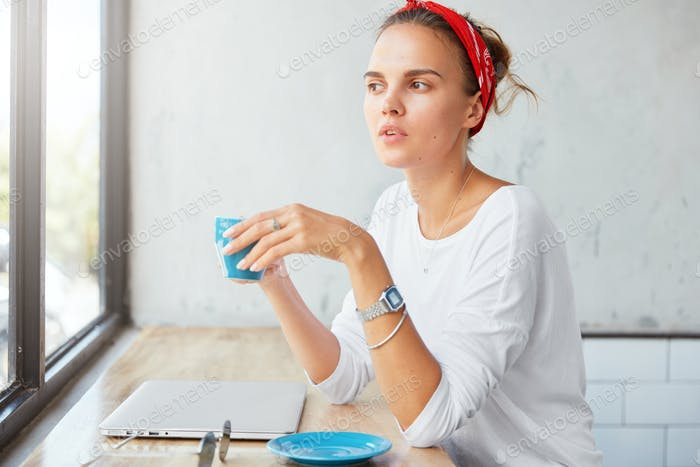 Stylish hipster girl uses laptop computer for remote work, has coffee break at coffeehouse, rests af