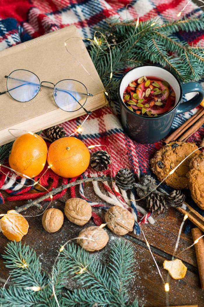 Hot tea with lemon and lingonberry leaves and other food and symbols of xmas