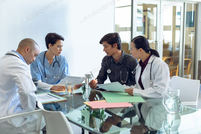 Diverse medical team  with stethoscopes around the neck discussing with each other at the table