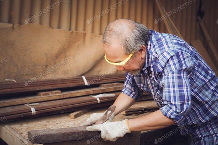Asian senior male carpenter using planer on wood board.