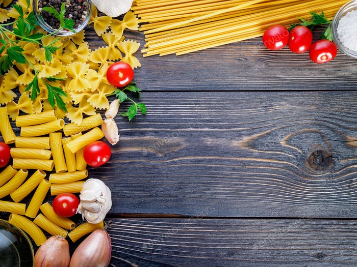 pasta, tomatoes, shallots, garlic, parsley on dark wooden background, top view, copy space.