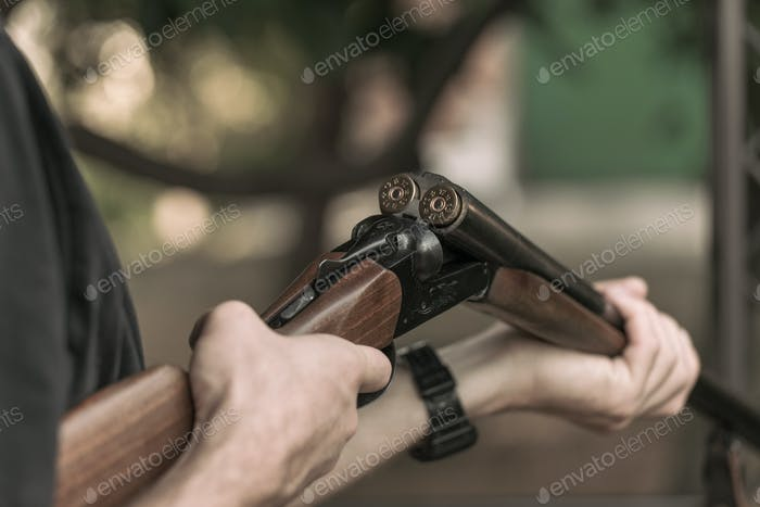 Man charging double-barreled hunting rifle closeup