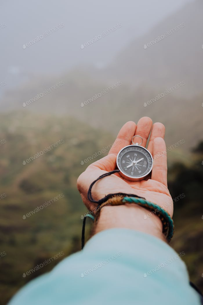 Starched palm with compass. Looking at the compass to figure out right direction. Foggy valley and