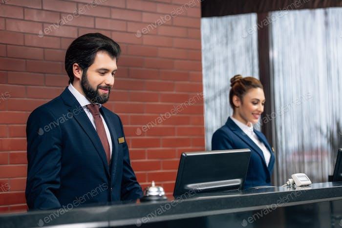 Hotelrezeptionisten arbeiten mit Computern am Schalter