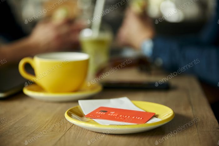 Credit card and bill on cafe table