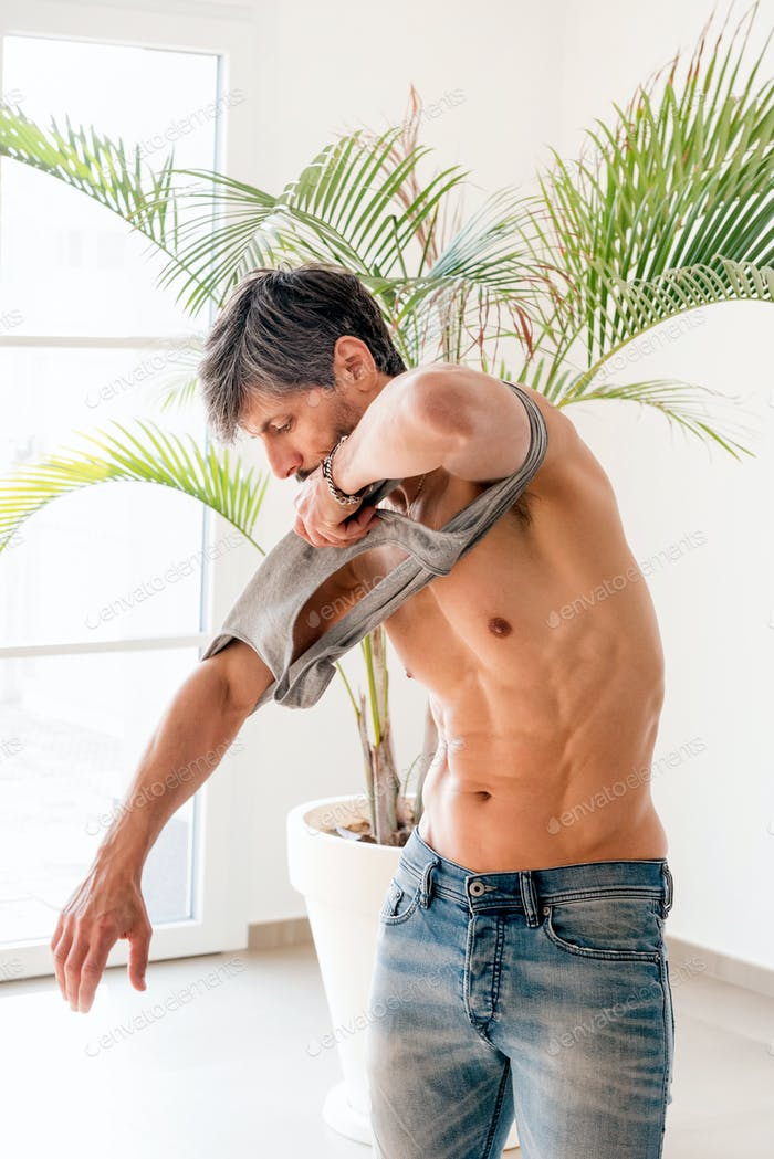 Fit toned fifty year old man showing his abdominal muscles