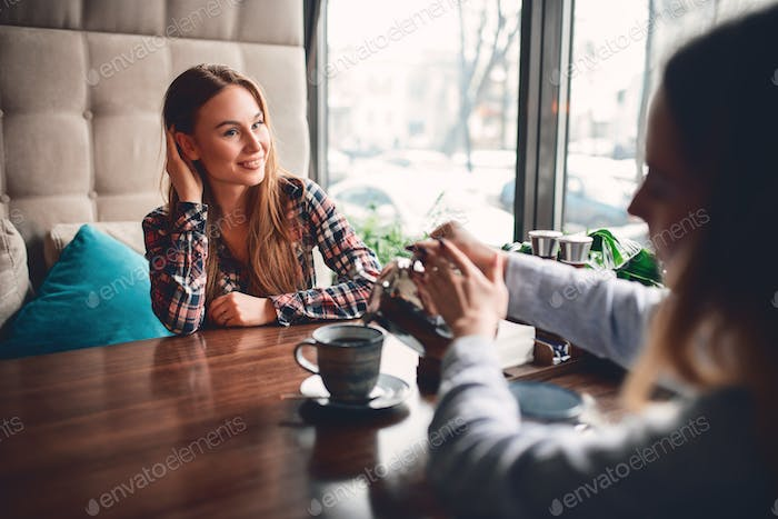 Woman pours coffee for her girlfriend in cafe