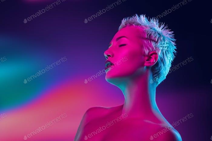 Portrait of female fashion model in neon light on dark studio background